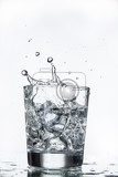 Fotografie glass with water and falling crystals of ice