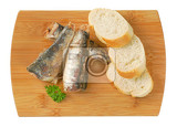 Fotografia sardines with slices of bread on wooden cutting board