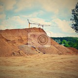 Fotografie pile of sand and construction of new homes concept for industry crane and blue sky with clouds and sun building construction site at sunset