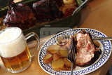 roasted pork knuckle with potatoes and beer as food background