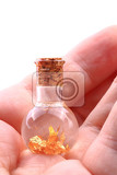 Fotografia gold in small glass bottle in human hand isolated on the white background