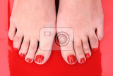 Photo red nails on the feet on the red background