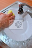 hand washing dishes hand with sponge and sink in kitchen washing dirty dishes  plate