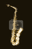 very old saxophone on the black background