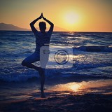 woman meditates  relaxes at sunset by the sea on the beach concept for yoga health and spa