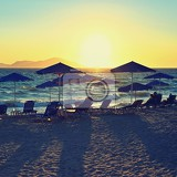 Fotografie sunbeds and umbrella on the beach at sunset by the sea beautiful concept for vacation summer holidays and travel