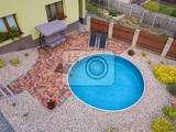 Fotografie small home swimming pool with two black sun loungers and rocking bench