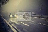 cars in the fog bad winter weather and dangerous automobile traffic on the road light vehicles in foggy day