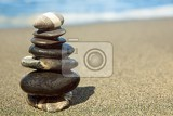 Fotografie stones pyramid on sand symbolizing zen harmony balance ocean in the background