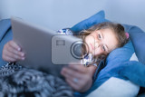 focused small cute girls using digital tablet in bed watching movie or play game in evening