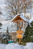 beautiful wooden signpost in winter garden covered with fresh snow