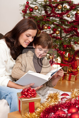 Young mother with son reading book on Christmas