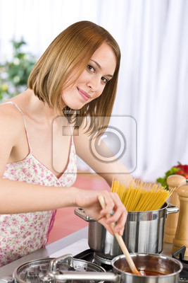 Cooking - Young woman tasting tomato sauce in kitchen