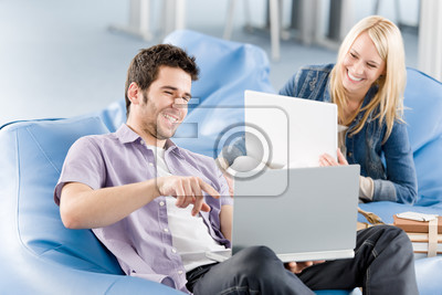 Young students at high-school pointing at laptop