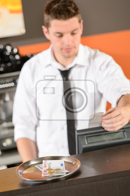 Young bartender in uniform taking cash euro