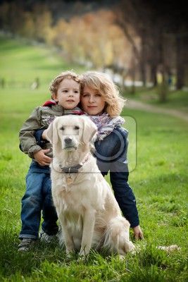 mother and son in the park along with a golden retriever