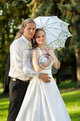 newlyweds in the park with umbrella