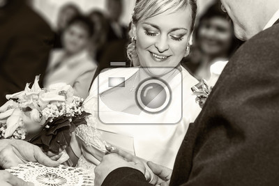 groom happy putting ring on smiling pretty woman brides finger black and white stock photo