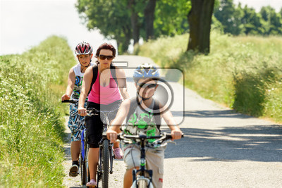 mother with two sons riding bike on bicycle trip focus to mother