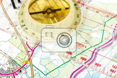 old touristic handheld compass on detailed territory map