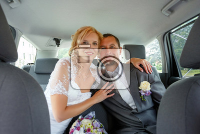 beautiful young wedding couple blonde bride with flower and her groom in car wide shoot