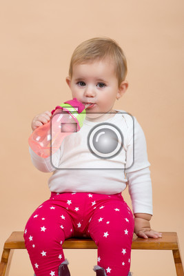 portrait of young cute baby with on beige background with bottle